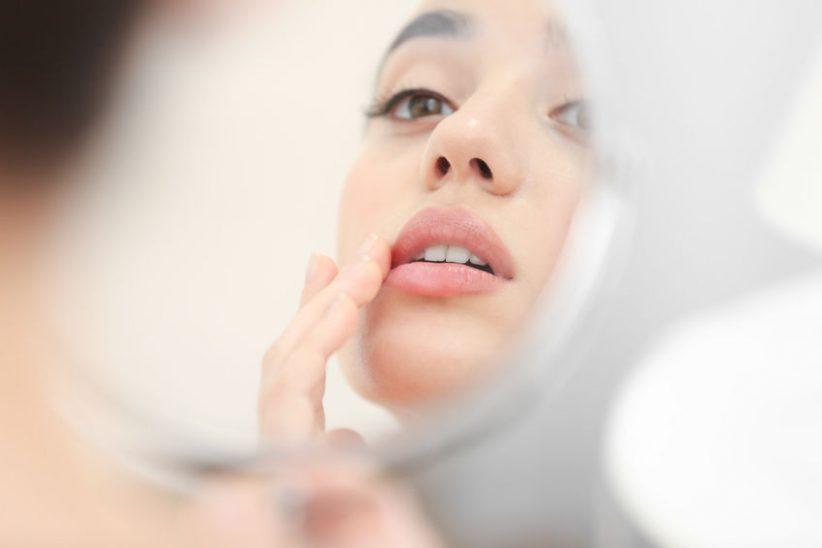Dame med herpes kigger i spejl